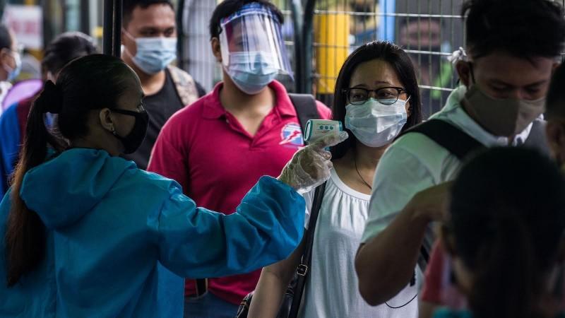 菲律賓衛生部8日通報指出,境內新增2539人確診,創下單日新高。圖為菲律賓工作人員替民眾量體溫。(法新社檔案照)