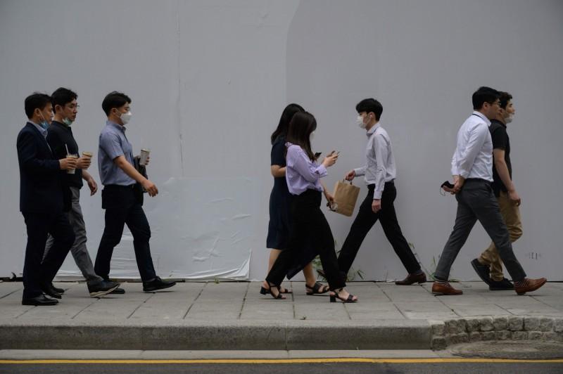 南韓境內疫情緊張,單日新增病例數再現6開頭,街上行人紛紛戴起口罩自保。圖為首爾街景。(法新社)