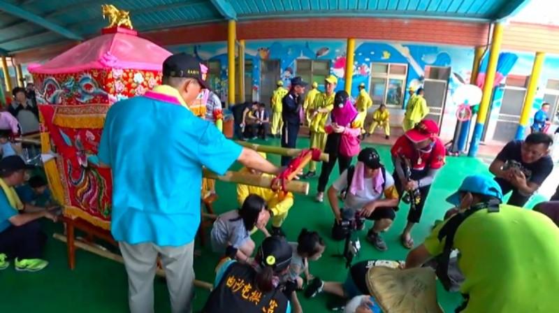 媽祖鑾轎進到幼兒園,讓孩子們鑽轎底,接受賜福。(記者詹士弘翻攝)