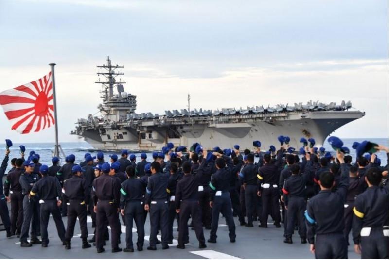 日本海上自衛隊兩艘練習艦日前在南海與美軍艦聯合操演,圖為日方官兵向遠方的美國雷根號航艦揮帽致意。(圖擷取自日本海上自衛隊官網)