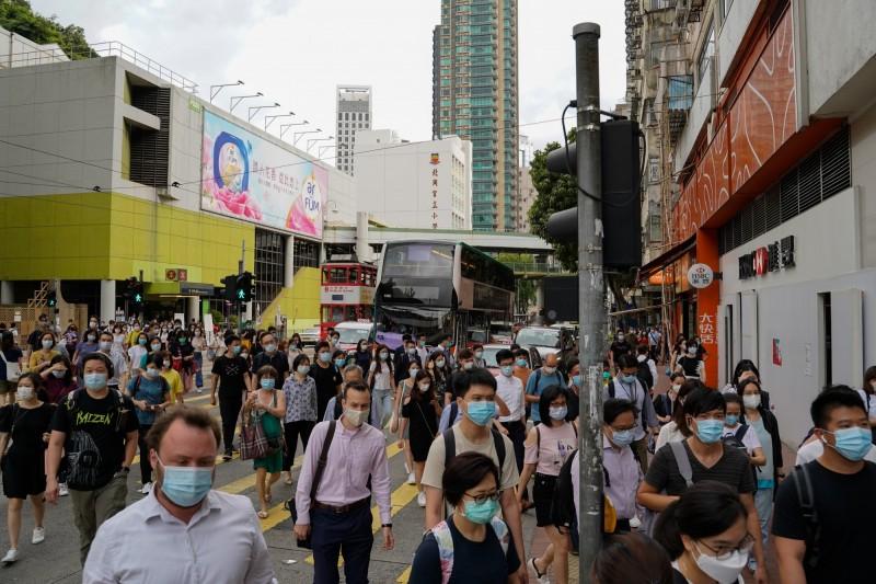 香港今天新增38例確診,其中11例同住一棟社區大樓。圖為香港民眾戴口罩防疫。(彭博)