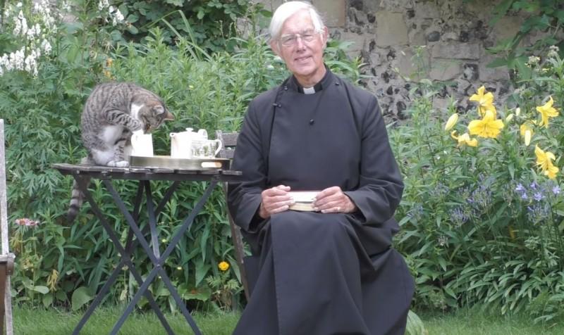 美國一名牧師威利斯(Robert Willis)日前透過線上直播的方式,來向信眾講道、晨禱,沒想到後面竟然有隻貓跳上桌子,直接喝起了牧師放在桌上的牛奶,超萌的畫面隨即引起關注。(圖擷自YouTube)