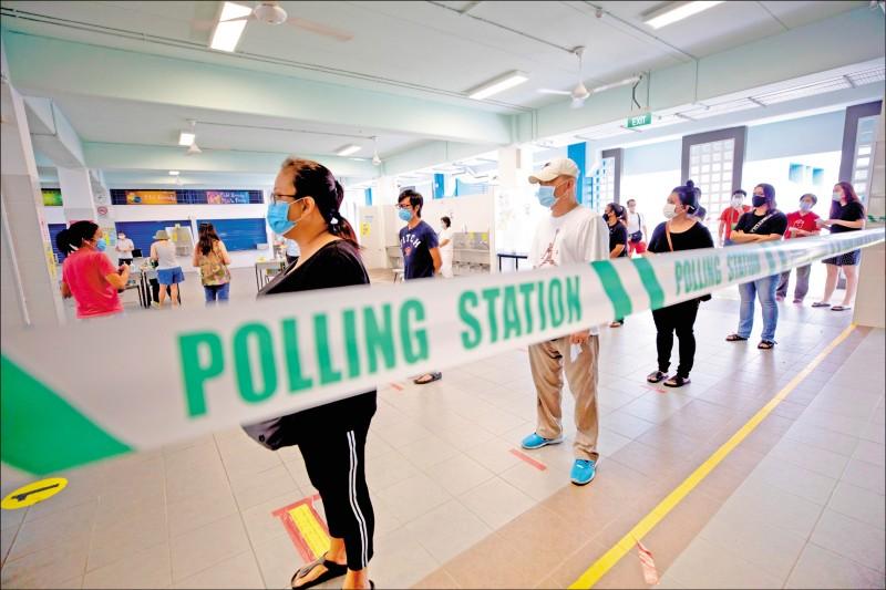 新加坡選民在投票時必須量體溫、保持社交距離,以防染疫。(歐新社)