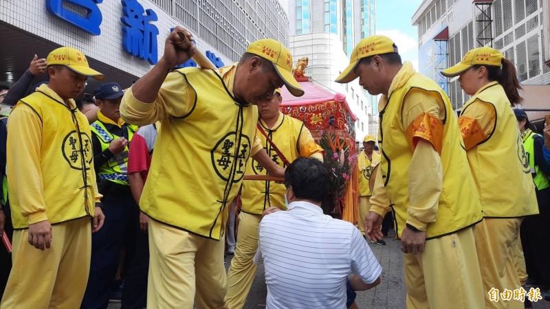 鹿寮成衣商圈業者抱著生病的孫子下跪。(記者張軒哲攝)