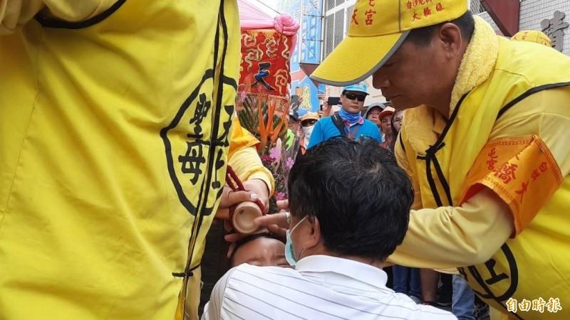 鹿寮成衣商圈業者抱著生病的孫子下跪,獲白沙屯媽祖賜福。(記者張軒哲攝)