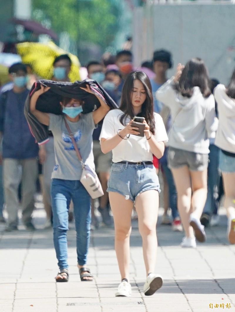 明(12)日全台天氣非常炎熱,12縣市亮高溫燈號,可能飆升至36度以上高溫,各地紫外線也都達「過量級」以上。(記者黃志源攝)