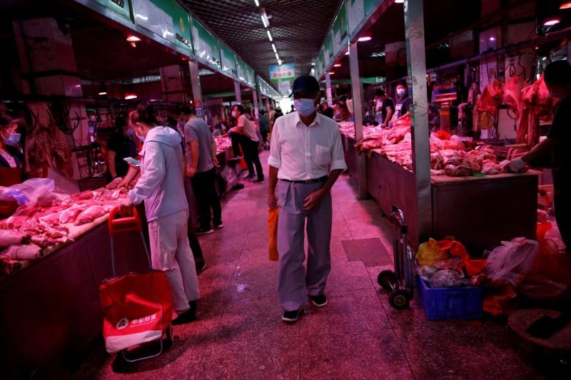 北京連續五日喊出單日零新增,中國10日單日新增病例2例。圖為北京民眾在市場採買情況。(路透)