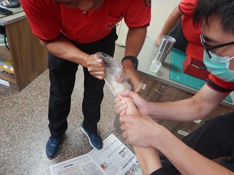 消防員以塑膠袋穿過玉鐲內側並反套,藉由沙拉油潤滑,最終以外推方式順利將玉鐲取下。(圖由嘉市消防局提供)
