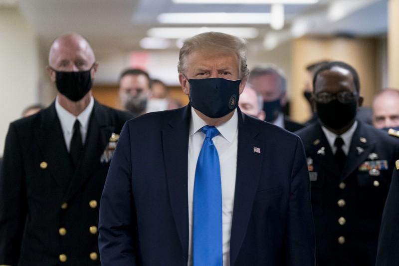 先前一向抗拒戴口罩的川普,11日訪問馬里蘭華特里德軍醫院時,難得地公開戴上口罩亮相。(彭博)