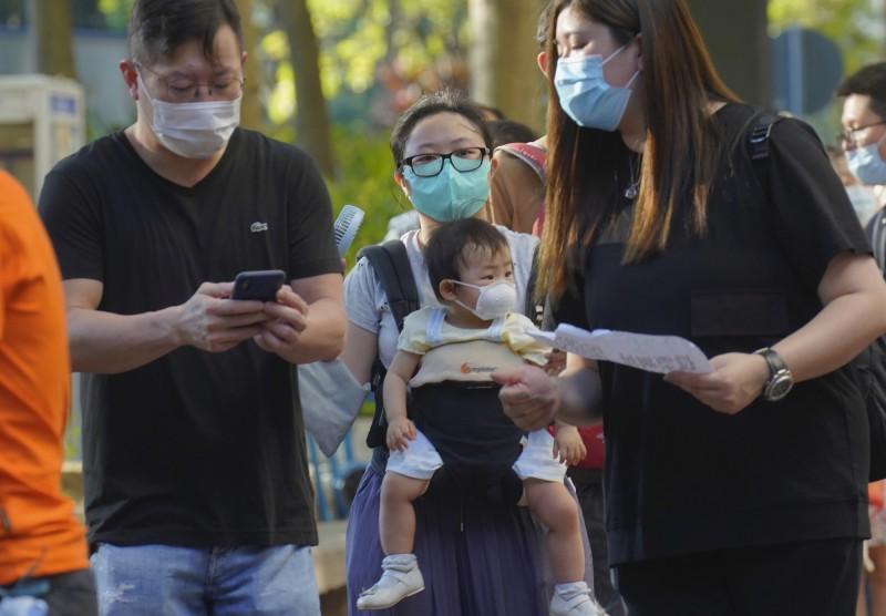 香港「民主派35+初選」投票結束,截至12日晚間11點,總投票人數已超過61萬,其中電子票數已達59萬2211張,紙本票數初估則有約2萬1千張。圖為香港今日一名母親抱著襁褓中的孩子排隊投票。(美聯社)