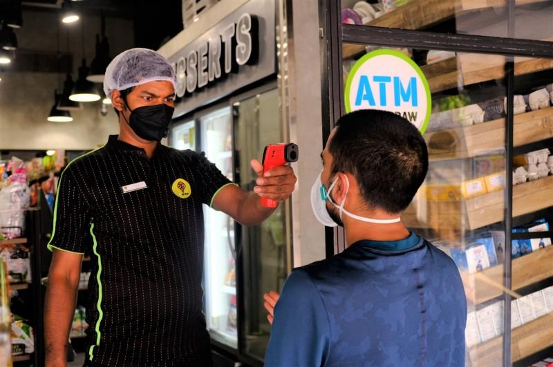 印度武漢肺炎確診病例12日逼近85萬例,南部科技重鎮班加羅爾所在省分將實施為期一週封鎖措施。圖為連鎖超商店員為顧客量體溫。(中央社檔案照片)