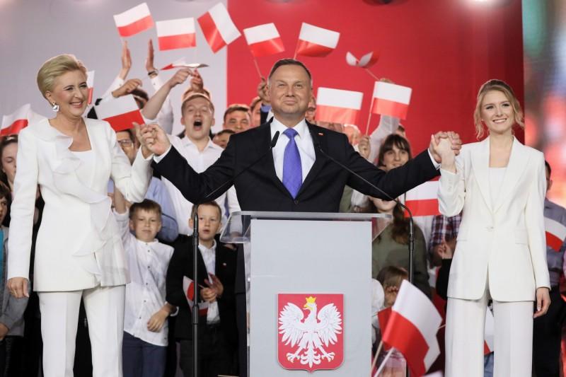 波蘭12日舉行總統大選第2輪投票,官方結果顯示,現任總統杜達(中)成功連任。(歐新社)