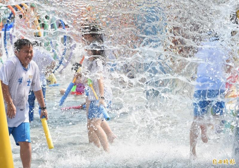今天各地天氣炎熱,台北測站上午11時59分測出攝氏38.9度高溫,創下7月最高紀錄。在剛揭幕的兒童新樂園「小小水樂園」中玩水的學生,則是搶先體驗新設施的清涼暢快。(記者劉信德攝)