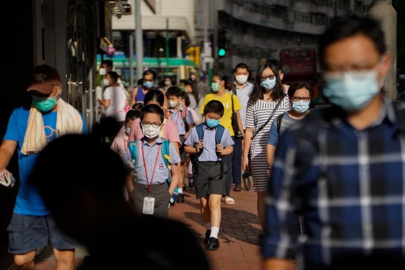 香港教育局發文要求學校,明起除考試外暫停所有校內活動2週。圖為香港民眾戴口罩防疫。(彭博)