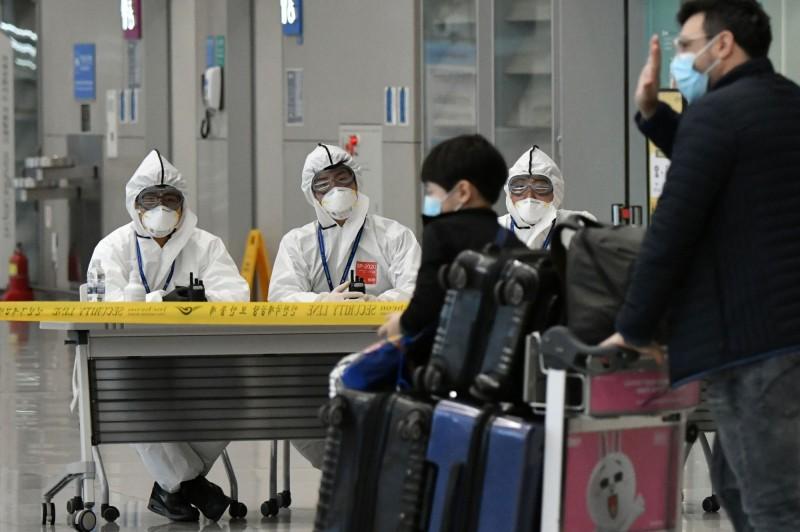 南韓已有連續19日境外移入病例保持二位數。圖為南韓仁川國際機場檢疫人員工作情況。(法新社)