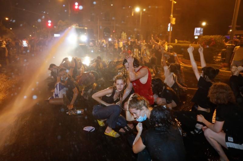 面對警方的強力抗暴水柱,示威群眾跪地仍堅定怒喊:「總理下台!」(法新社)