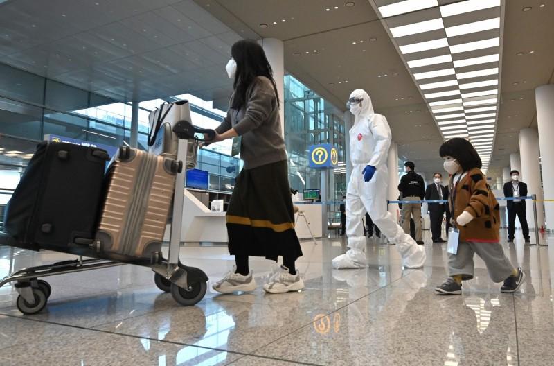 圖為南韓仁川國際機場檢疫人員引導返國民眾配合入境檢疫情況。(法新社)