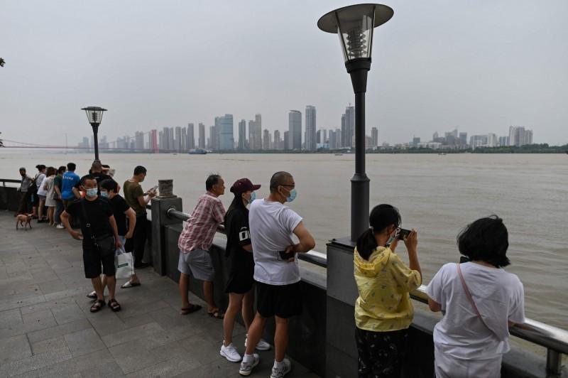 中國水利部指出,長江中下游預計7月底至8月中旬才會退至警戒水位以下。圖為中國武漢民眾觀看長江洪水。(法新社)