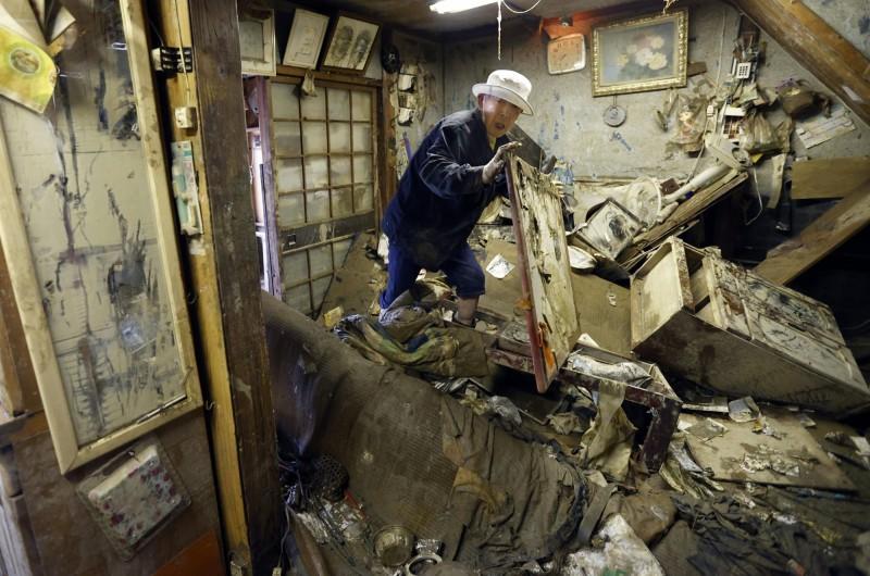 熊本縣人吉市一名長者返回滿目瘡痍的家園尋找藥物。(美聯社)