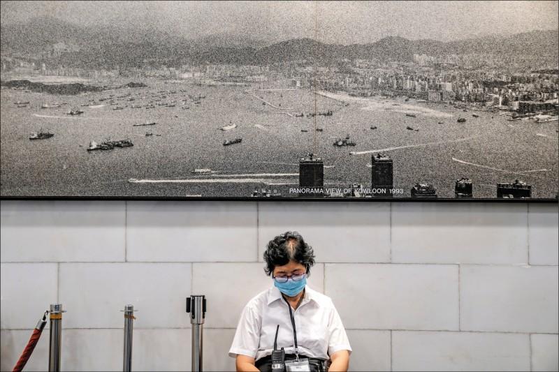 美國總統川普簽署「香港自治法」,未來美國將據此制裁損害香港自治的中國官員與金融機構。圖為一名婦女15日坐在描繪香港九龍的照片前。(彭博)
