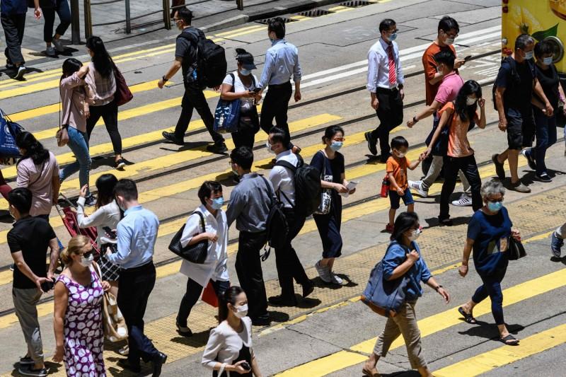 香港今日新增的67例確診中,有63例為境內感染。圖為香港中環行人皆配戴口罩。(法新社)