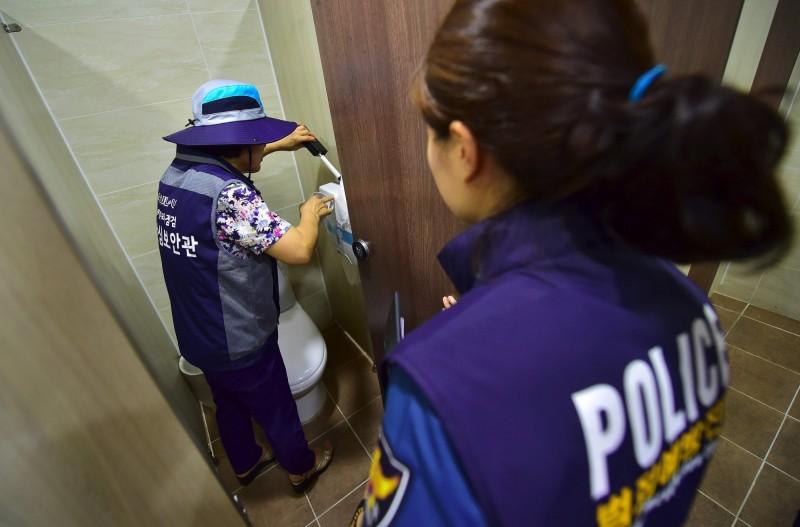 南韓教育部下令「全面」檢查全國的小學、中學、高中,搜查校內是否藏有隱藏式攝影機。圖為南韓執法人員在首爾的女廁檢查是否有偷拍裝置。(法新社)