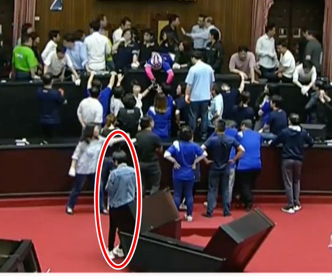 主席台上藍綠立委正在混戰,賴品妤在台下淡定PO文的身影被攝影機錄下。(圖擷自貓與邪佞的手指)