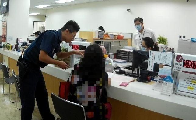 張婦要匯款給假醫生,保七警員與台銀人員在櫃檯前不斷勸說。(記者陳賢義翻攝)