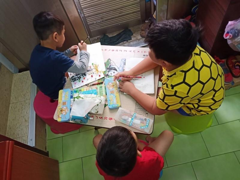 家扶扶助的阿銘3兄弟,家境受疫情影響更貧困,只能窩在一張小桌子上寫作業,拿到3倍券也只能付學費和生活費,無望更換新書桌。(記者蔡淑媛翻攝)