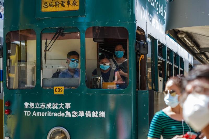 香港今新增58例武漢肺炎確診案例,其中50例為本土案例,源頭不明的個案懷疑是社區傳播導致。香港民眾上街持續戴著口罩做好防疫工作。(彭博)