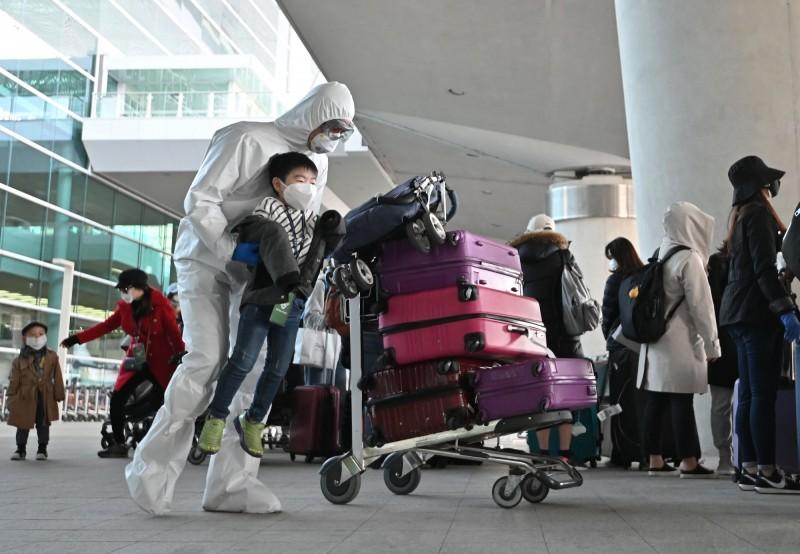南韓外交部昨宣布延長全球旅遊特別預警至8月19日。圖為南韓仁川國際機場檢疫人員協助返國公民接受檢疫情況。(法新社)