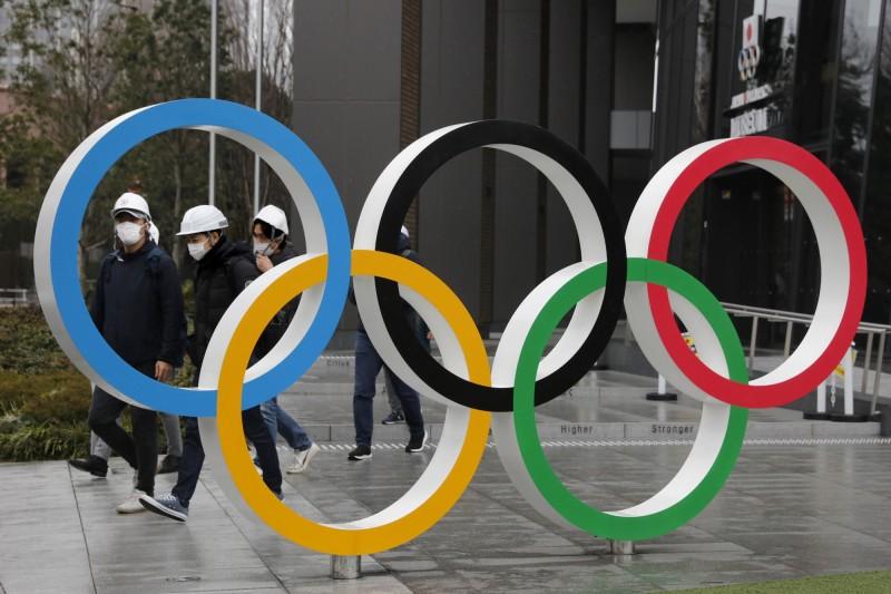 戴口罩的民眾經過東京新國立競技場。(資料照)