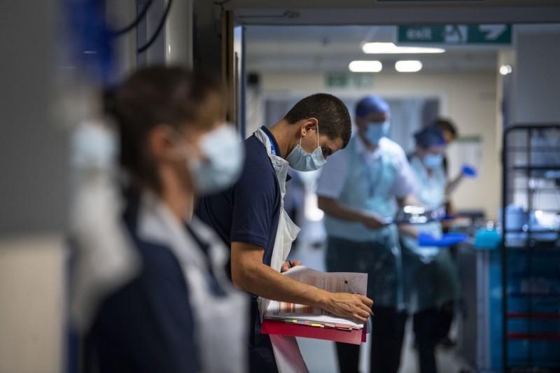 英國和義大利開始為有武肺後遺症的人提供康復服務。圖為醫療人員檢查患者的病歷。(法新社)