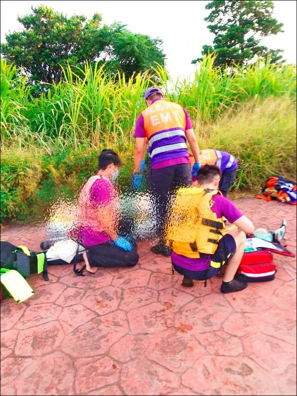 消防人員把范姓婦人救上岸後,由救護人員接手急救。 (記者李容萍翻攝)
