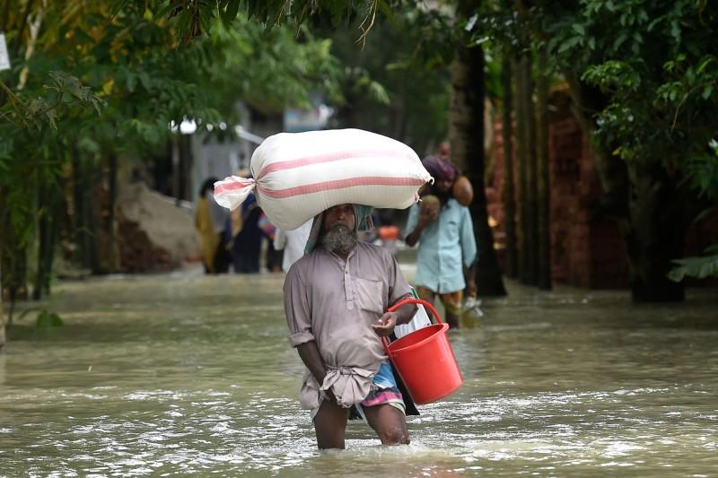 隨著南亞地區進入雨季,近日印度東北部、尼泊爾以及孟加拉皆發生嚴重的水災,目前3國至少共有221人死亡,並有超過100萬人被迫流離失所。圖為孟加拉的災情。(法新社)