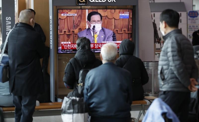南韓群聚感染案例以新天地教會案影響最為嚴重。圖為3月2日南韓民眾收看新天地教會教主李萬熙道歉記者會畫面。(美聯社)