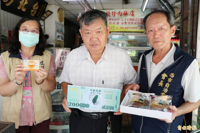嘉市西市場自治會長郭義文(右一)與攤商(中)邀民眾來市場消費三倍券。(記者丁偉杰攝)
