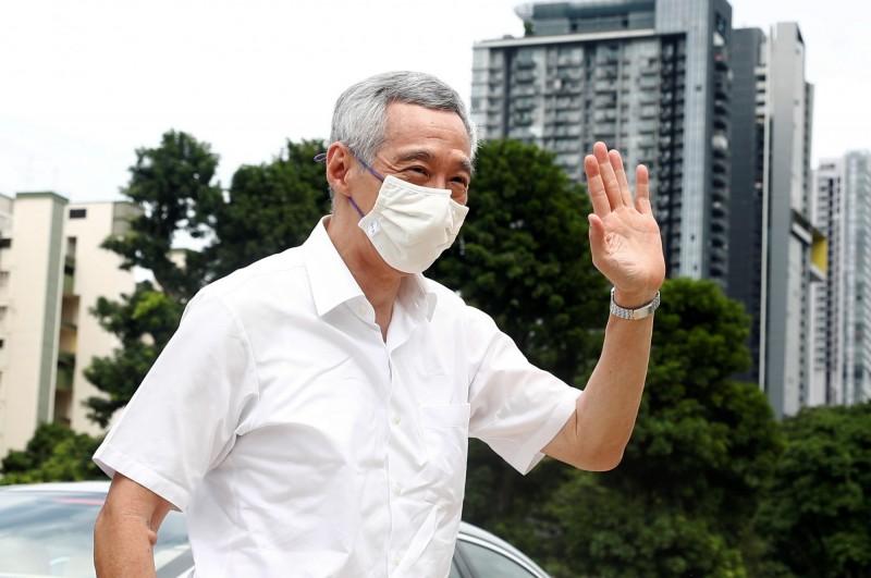 新加坡總理李顯龍7月10日大選投票日在投票所外和民眾打招呼。(路透)