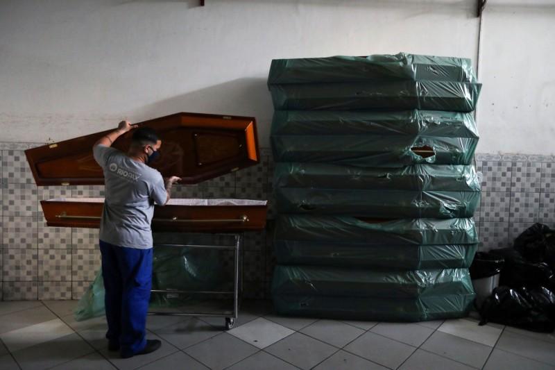 圖為巴西里約一名葬儀社工人準備棺材情況。(路透)