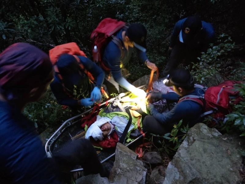 王女因跌落山谷受傷,消防人員上山以接力搬運方式將她抬下山就醫。(記者歐素美翻攝)