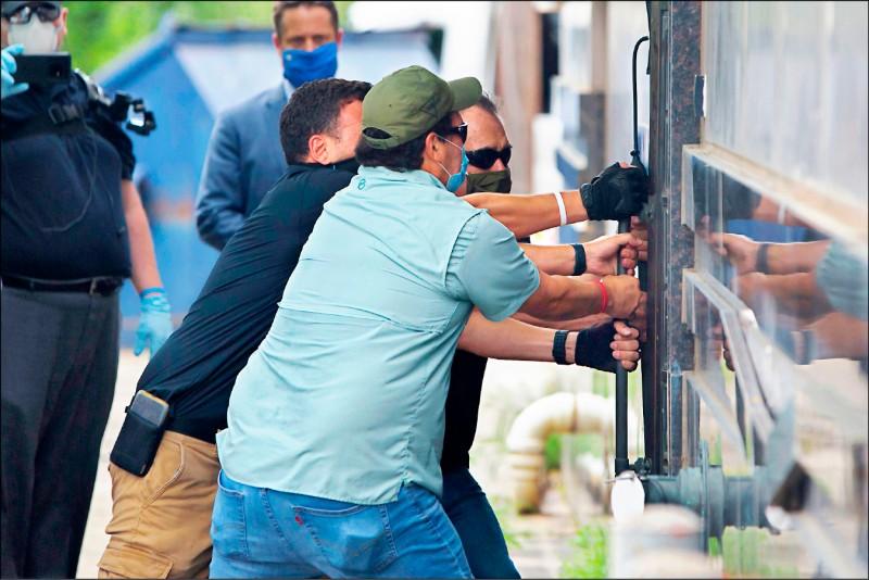 中國駐休士頓總領事館24日如期關閉,美國執法人員在中方外交人員撤離後,合力拉開總領事館的後門入內。(法新社)