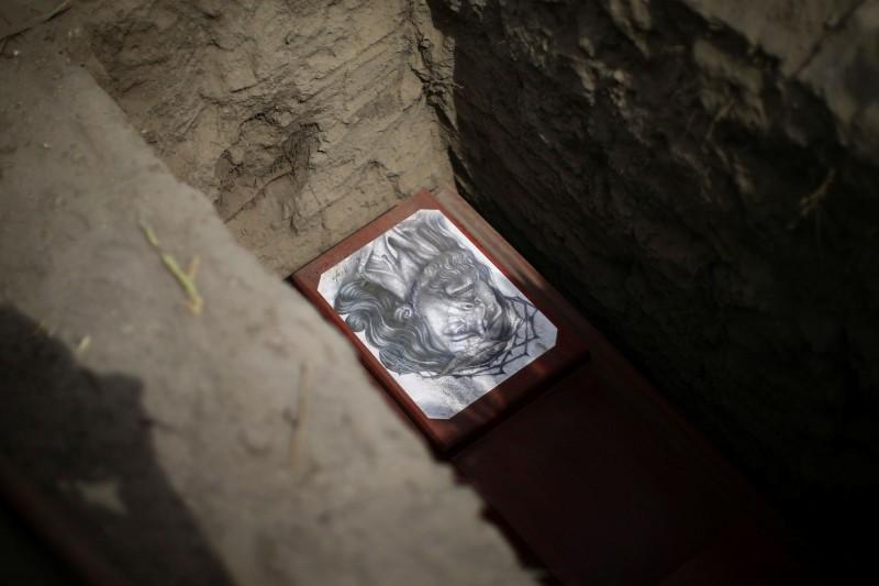 美洲國家狀況嚴峻,境內病例每日仍以驚人幅度增長。圖為墨西哥一位武漢肺炎死者的陪葬耶穌畫像。(路透)