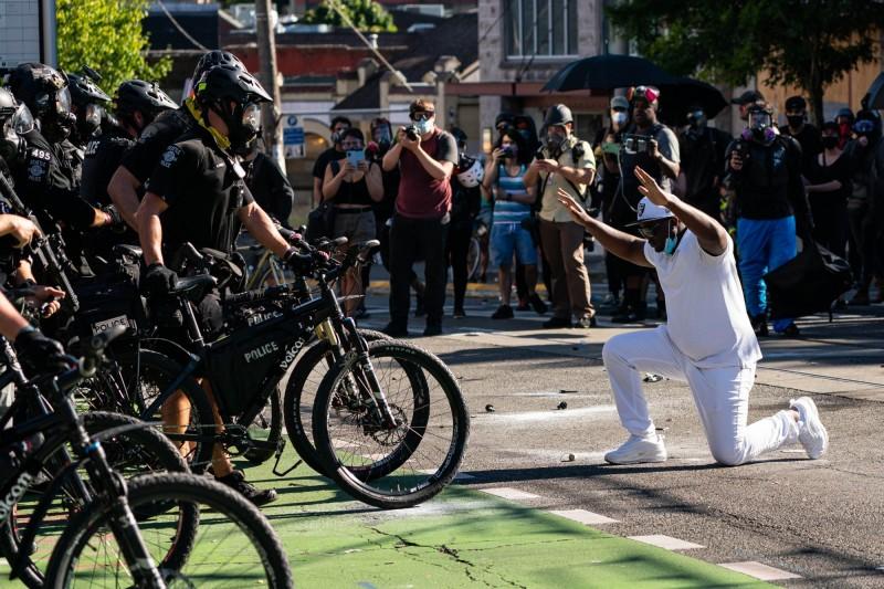 一名示威者向西雅圖警方下跪並高舉雙手。(法新社)