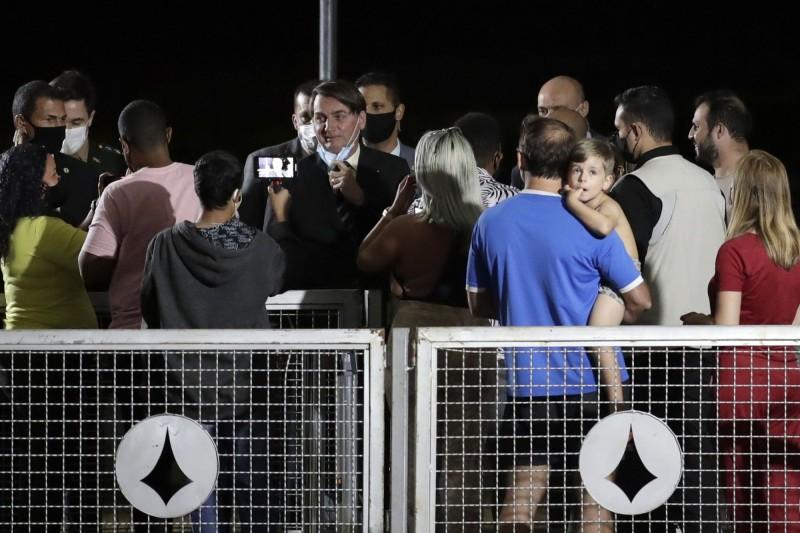 巴西總統武漢肺炎篩檢由陽轉陰病癒,27日在官邸外樂摘口罩與支持者合影。(美聯社)