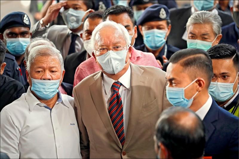 馬來西亞前首相納吉廿八日在人群簇擁下走入法院,為一馬弊案的判決出庭聽判。(美聯社)