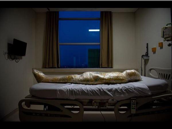 有位印尼的新聞攝影師拍下一張因疫情去世,遺體被塑膠模緊緊包裹住進行防疫處理後,放在病床上的照片,攝影師坦言「這是自己拍過最令人心碎、最恐懼的照片」。(圖擷取自Joshua Irwandi IG)