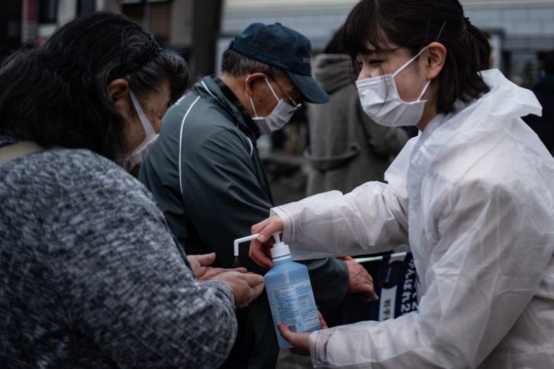 日本岩手縣今天出現2名武漢肺炎感染者,全國唯一零感染的「淨土」神話破功,圖為岩手縣民眾參加活動時,工作人員為民眾消毒的畫面。(法新社)