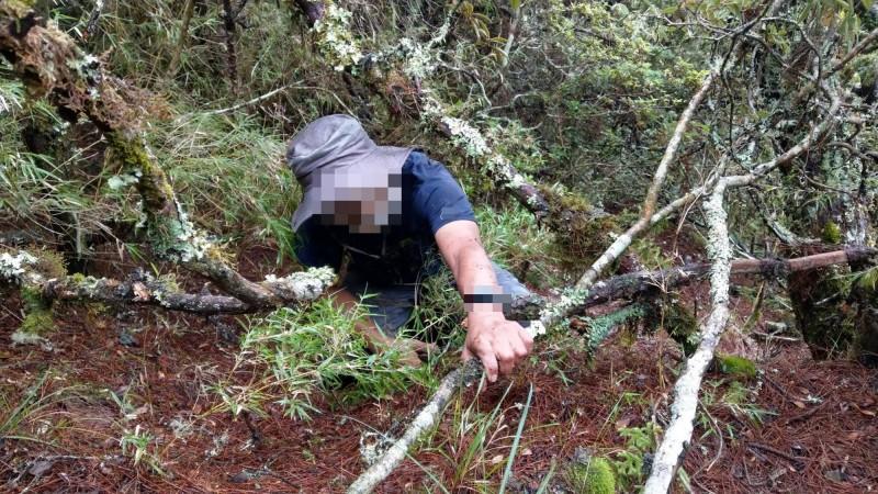 獨攀迷路的山友受困在畢祿山9.4-9.5K附近的矮樹林裡,努力攀住樹枝往上。(南投縣消防局提供)