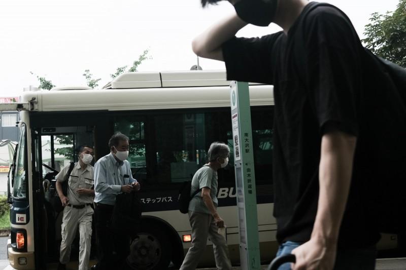 日本政府推行「Go To Travel」計畫,盼振興國旅,但近期各地陸續傳出新疫情。圖為東京都八王子市一處公車站。(彭博)