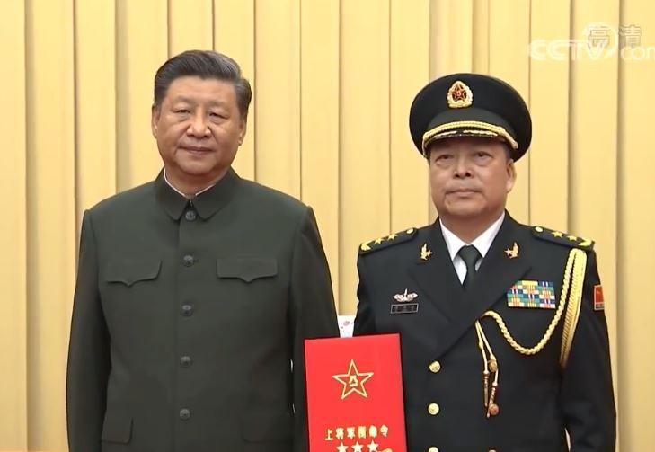 中國國家主席習近平向晉升上將的火箭軍政治委員徐忠波頒發命令狀。(圖擷取自央視)